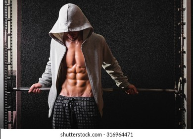 Muscular young man in gray hoodie in gym posing. Fit slim guy in gray sportswear posing against dark gray background. Medium retouch, no filter, horizontal, copy space.