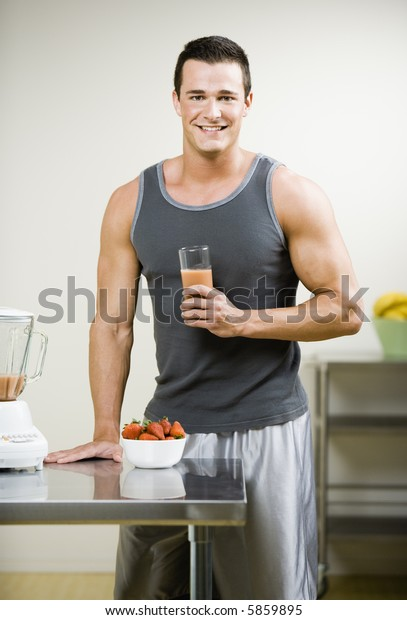 Muscular Young Man with Juice Smoothie