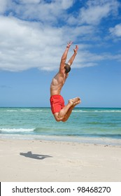 muscular young man jumping on the beach