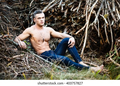 Muscular young man with naked torso in a heap of branch.