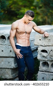 Muscular young man near concrete slab.