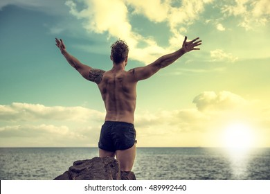 Muscular young man on the beach seen from the back, with arms open enjoying the sensation of freedom in front of rising or setting sun