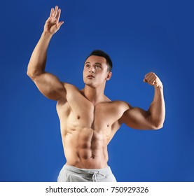 Muscular young man on color background