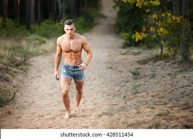 Muscular young man running at forest.