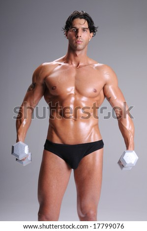 918916ea7f0b Muscular young man shirtless in briefs and sweaty working out lifting  weights