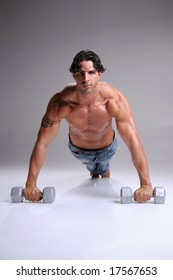 Muscular young man shirtless and sweaty in jeans working out doing push ups