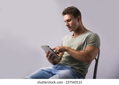 Muscular young man sitting on chair reading from ebook device, pointing finger at screen