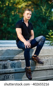 Muscular young man sitting on concrete slab
