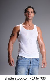 007b60e27da15 Muscular young man standing in jeans and a white wife beater tee shirt