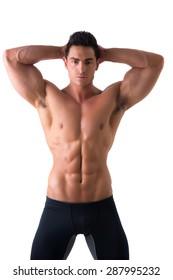 Muscular young man standing and looking at camera smiling, shirtless, wearing tight black shorts
