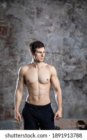Muscular young man in a studio. Portrait of strong brutal guy naked torso.