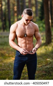 Muscular young man with sunglasses in a forest.