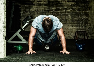 Muscular young man in sweaty shirt training burpee with kettlebells on the gym floor with selective focus and film grain