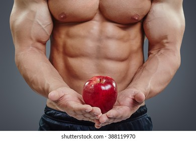 Muscular young man torso and red apple in hands