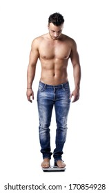 Muscular young man weighing himself on scale, isolated on white background