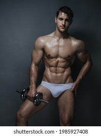 Muscular young man in white underwear with dumbbell in studio at grey background
