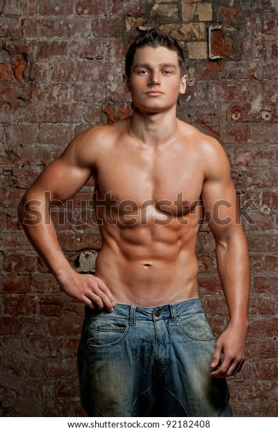 Muscular Young Guy Posing In Jeans And Naked Torso Stock