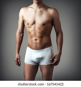 Muscular young sexy handsome man posing in white underwear on gray background
