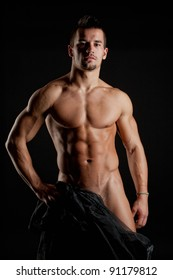 Muscular young sexy naked cute man wrapped in black silk