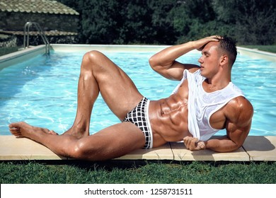 9f78996398 Muscular young sexy wet guy in swimwear and white tank top near the pool  outdoors