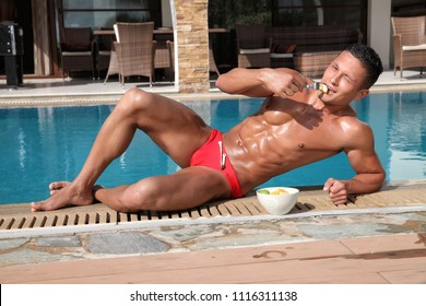 5501ef74de Muscular young sexy wet naked smiling guy in red swimwear eating fruit near  the pool outdoors