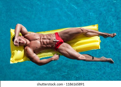 Muscular young sexy wet naked man in red underwear lying on yellow inflatable mattress in pool