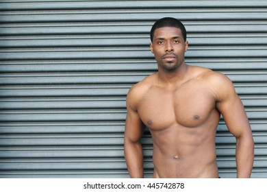 Muscular young sexy wet naked cute African man posing in trunks with copy space