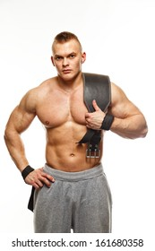 Muscular young sportsman with weight lifting belt