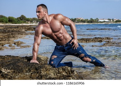 Muscular young wet naked athletic sexy man posing on the beach with naked torso in blue jeans
