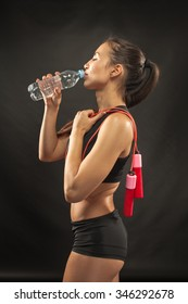 Muscular young woman athlete  with a skipping rope drinking water on black background.