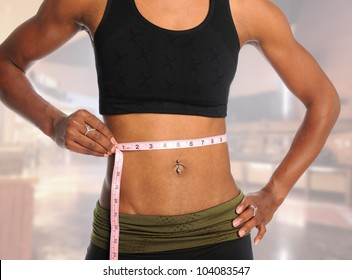 Muscular young woman measuring waist with tape isolated over blurred background