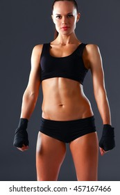 Muscular young woman standing on gray background.