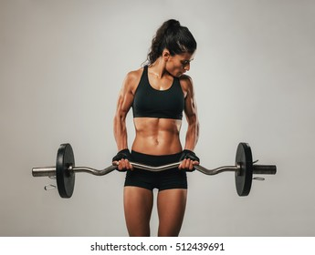 Muscular young woman using curved barbell while looking at muscles bulging in her arms
