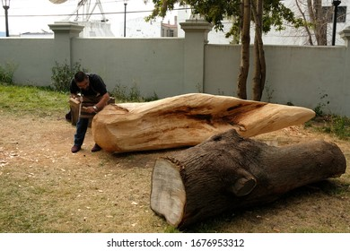 Museo Regional de Magallanes. Punta Arenas, Chile  - February 28 2020 - An artist who carves a wooden trunk in front of the Museum
