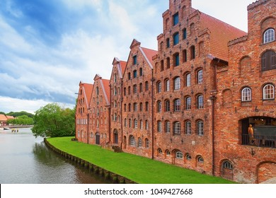 Museum Holstentor of city Lubeck, northern Germany, June 2017. River Trave. Traditional brick gothic architecture.