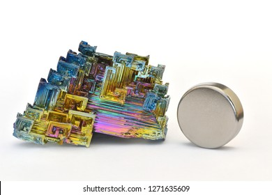 MUSEUM MINERAL SERIES: Bismuth crystals and a neodymium magnet. Bismuth is the most strongly diamagnetic element and also the heaviest that is not radioactive. White background.