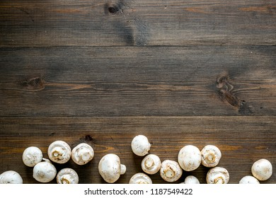 Mushroom champignons. Fresh raw whole champignons on dark wooden background top view space for text
