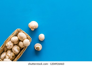 Mushroom champignons. Fresh raw whole champignons in basket on blue background top view copy space