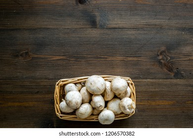 Mushroom champignons. Fresh raw whole champignons in basket on dark wooden background top view space for text