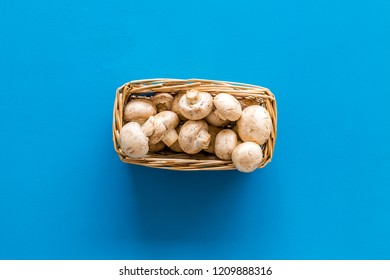 Mushroom champignons. Fresh raw whole champignons in basket on blue background top view space for text