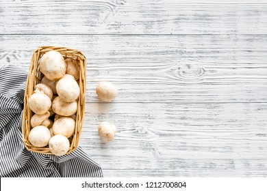 Mushroom champignons. Fresh raw whole champignons in basket on grey wooden background top view copy space
