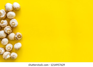 Mushroom champignons. Fresh raw whole champignons on yellow background top view copy space
