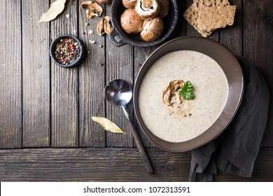 Mushroom cream soup in a bowl over dark wooden background, top view