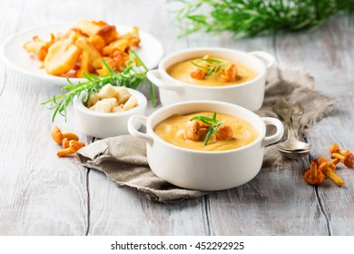 Mushroom cream soup with chanterelles and herbs on a white rustic wooden background, selective focus
