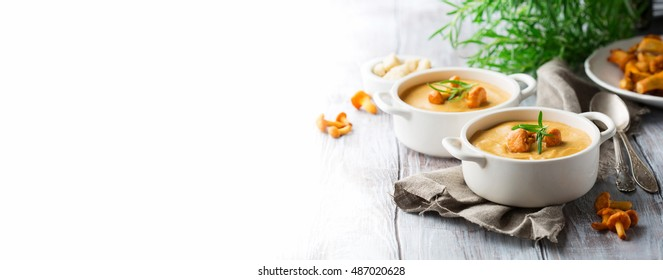 Mushroom cream soup with fresh chanterelles and herbs on a white rustic wooden background, selective focus. Autumn concept. Long web format