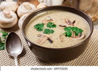 Mushroom cream soup with herbs and spices in brown bowl