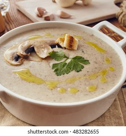 Mushroom cream soup on a table, with bread, garlic, and raw mushrooms on a white chopping board. Salt and Pepper on the table.