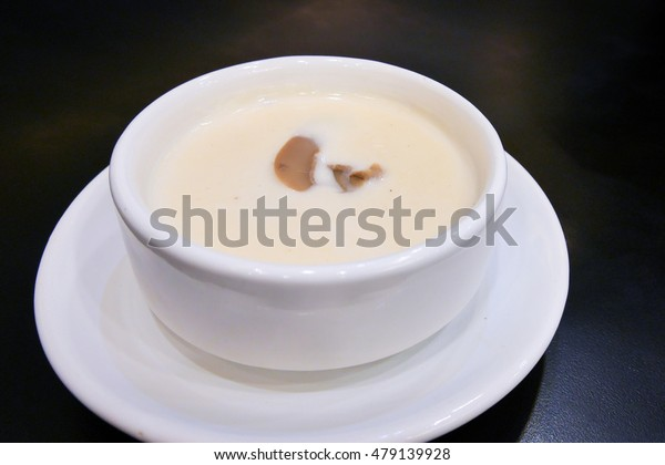 Mushroom cream soup in a white bowl  on black background