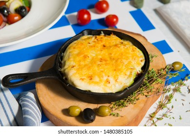 Mushroom julienne with olives on a table against the background of the flag of Greece close-up.