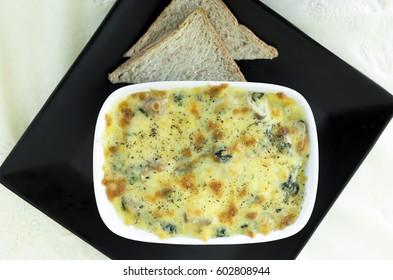 mushroom lasagna dish in baking dish with sliced bread - vetgetarien food
